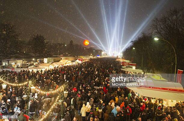 Revellers attending the public party crowd the 'Strasse des 17 Juni' avenue as Berlin's landmark Brandenburg Gate is illuminated to celebrate the New...
