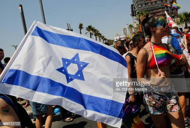 Revellers carrying an Israeli national flag celebrate along a sea side avenue in Tel Aviv during the city's annual Gay Pride parade on June 8 2018...