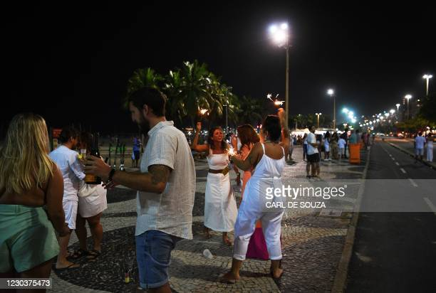 Revellers celebrate New Year's Eve at Copacabana beach, Rio de Janeiro, Brazil on December 31, 2020. - Brazil rang in the New Year with Rio de...