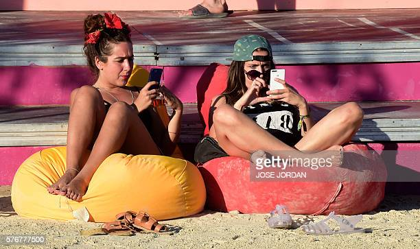 Revellers check their mobile phone as they rest on the fourth day of the 2016 Benicassim International Festival in Benicassim in Castellon province...
