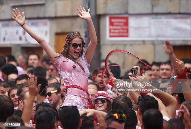 Revellers cheer and throw red wine during the opening and the firing of the 'Chupinazo' rocket which starts the 2014 Festival of the San Fermin...