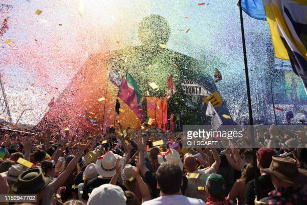 Revellers cheer as Australian singer Kylie prepares to perform at the Glastonbury Festival of Music and Performing Arts on Worthy Farm near the...
