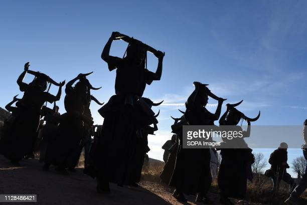 Revellers covered in oil and soot carrying bull horns on their heads and cowbells on a belt representing the devil are seen during a traditional...