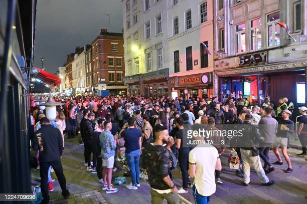 Revellers crowd the street outside bars in the Soho area of London on July 4 as restrictions are further eased during the novel coronavirus COVID-19...