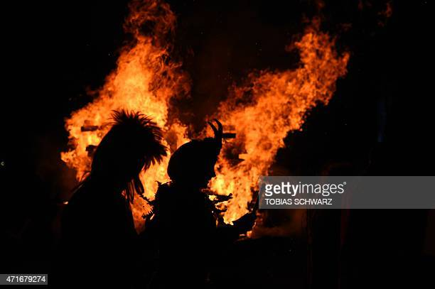 Revellers dance around a fire as they take part in Walpurgis Night celebrations at the film park in Babelsberg Potsdam near Berlin on April 30 2015...