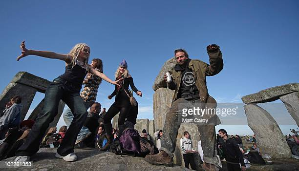 Revellers dance in front of the stones as the midsummer sun rises just after dawn over the megalithic monument of Stonehenge on June 21 2010 on...
