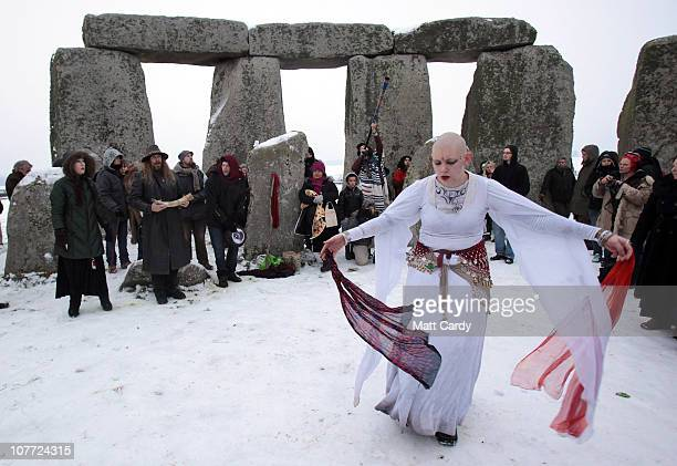 Revellers dance in the snow after druids conducted a sunrise service at Stonehenge on December 22 2010 in Wiltshire England Hundreds of people...