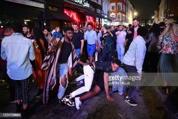TOPSHOT Revellers dance in the street in the Soho area of London on July 4 following a further easing of restrictions to allow pubs and restaurants...