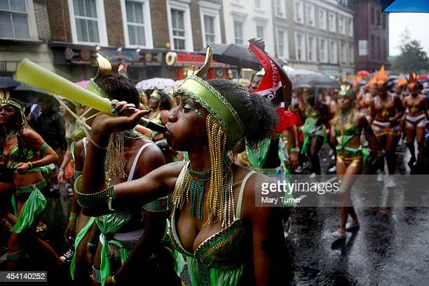 Revellers dance through the rain soaked streets of West London during the Notting Hill Carnival on August 25th 2014 in London England Despite the bad...