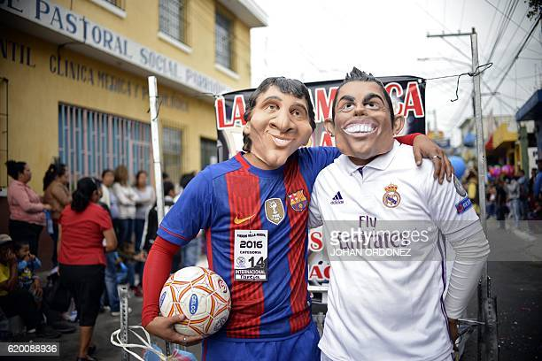 Revellers disguised as Argentinian footballer Lionel Messi of Spain's Barcelona and Portuguese Cristiano Ronaldo of Spain's Real Madrid take part in...