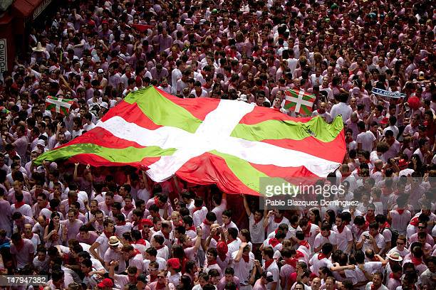 Revellers display a giant Ikurrina flag of the Basque Country during the opening day or 'Chupinazo' of the San Fermin Running Of The Bulls fiesta on...