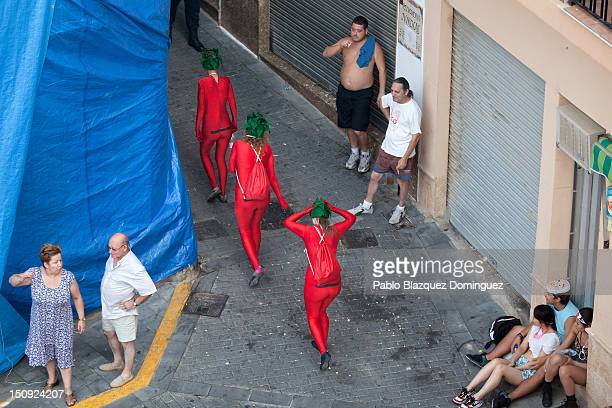 Revellers dressed a tomatoes walk in the streets during the annual Tomatina festival on August 29 2012 in Bunol Spain An estimated 35000 people threw...