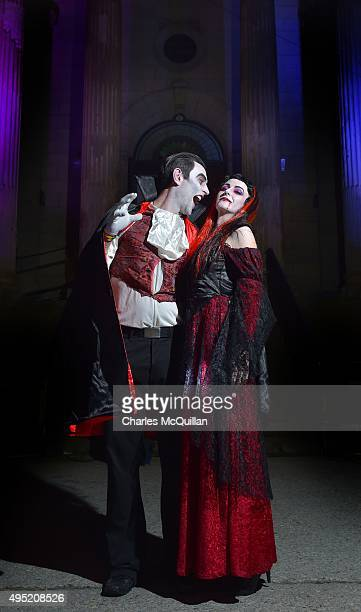Revellers dressed as a vampire couple pose for photographs as they arrive for a Gothic Ball taking place inside a former church on October 31 2015 in...