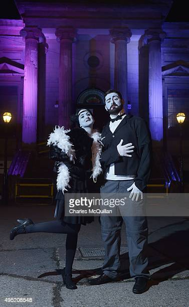 Revellers dressed as black and white movie stars pose for photographs as they arrive for a Gothic Ball taking place inside a former church on October...