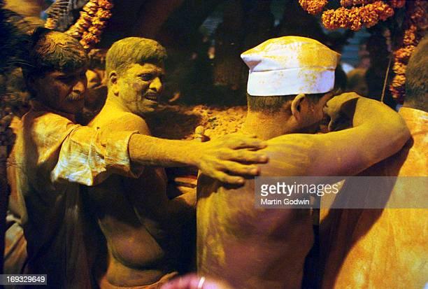 Revellers dressed in whilte clothes or bare chested covering each other in yellow turmeric powder during a Hindu Festival with garlands of orange...