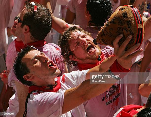 Revellers drink wine during the opening day or 'Chupinazo' of the San Fermin Running of the Bulls fiesta on July 6 2007 in Pamplona SpainFighting...