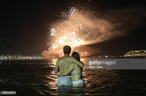 Revellers embrace as fireworks explode to ring in the New Year above Copacabana beach on January 1 2016 in Rio de Janeiro Brazil More than one...
