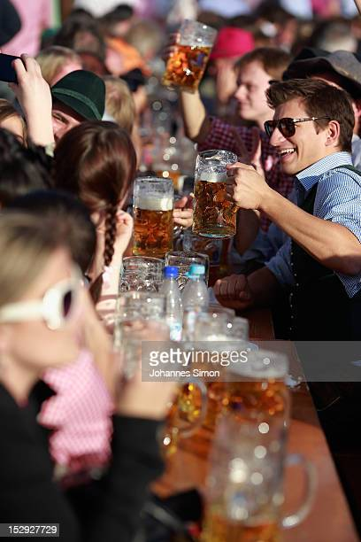 Revellers enjoy themselves as they drink beer outside the Loewenbraeu beer tent during day 7 of Oktoberfest beer festival on September 28 2012 in...