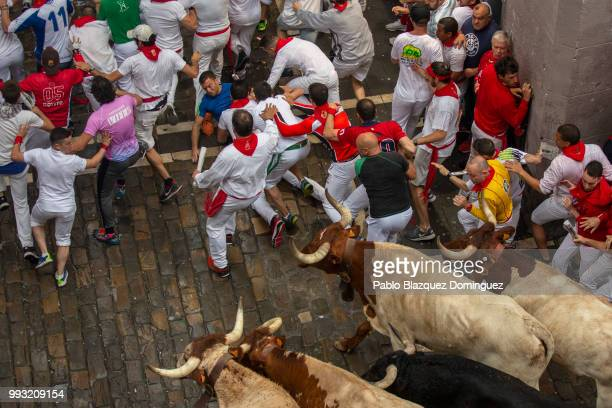 Revellers fall as they run with Puerto de San Lorenzo's fighting bulls during the second day of the San Fermin Running of the Bulls festival on July...