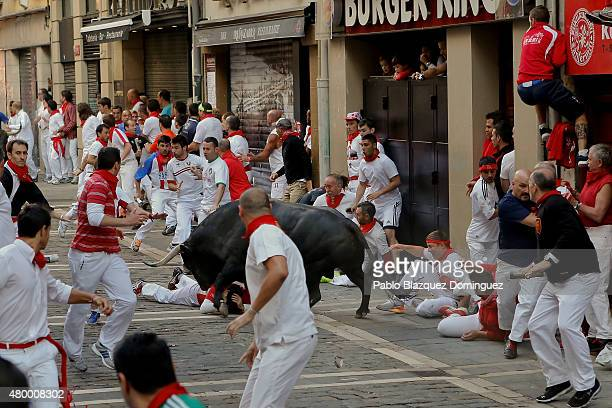 Revellers fall on the ground while running with the Victoriano Del Rio Cortes fighting bulls entering Estafeta Street during the fourth day of the...