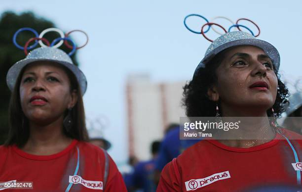 Revellers from the Uniao da Ilha do Governador samba school wear Olympic rings on their hats during a preCarnival rehearsal at the Sambodrome on...