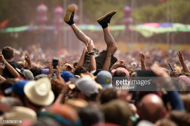 Revellers help a man crowdsurf as they watch The Slaves perform on The Other Stage at the Glastonbury Festival of Music and Performing Arts on Worthy...