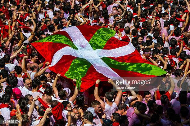 Revellers hold up a Basque Country's flag as they enjoy the atmosphere during the opening day or 'Chupinazo' of the San Fermin Running of the Bulls...