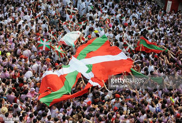Revellers hold up a Basque flag during the Chupinazo marking the first day of the San Fermin runningofthebulls on July 6 2011 in Pamplona Spain...