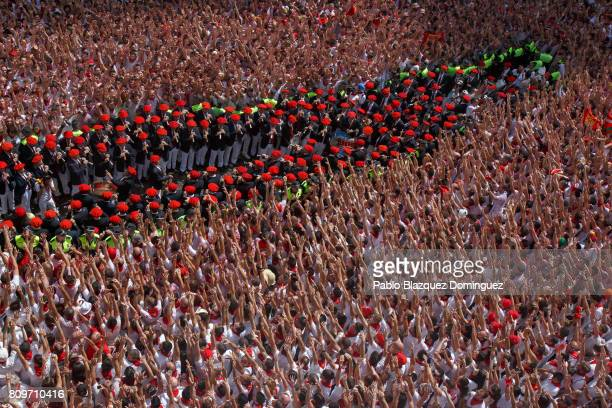 Revellers hold up their hands as they enjoy the atmosphere during the opening day or 'Chupinazo' of the San Fermin Running of the Bulls fiesta on...