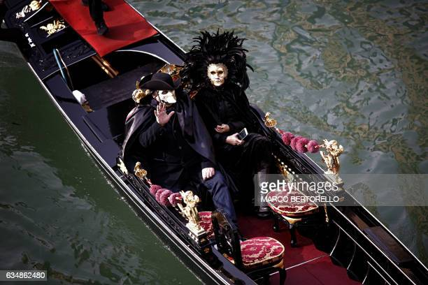 Revellers in a gondola wave during the masquerade parade on Grand Canal during Venice Carnival on February 12 2017 in Venice / AFP PHOTO / Marco...