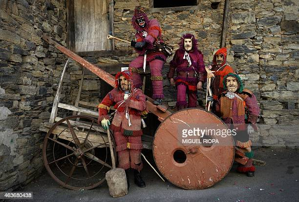 Revellers in carnival garb and wooden mask pose on a wooden cart during the traditional Celtic carnival 'Caretos' in the Portuguese village of Vila...