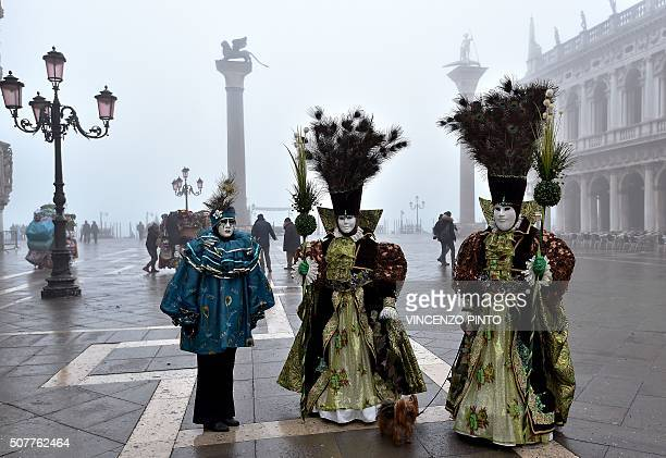 Revellers in costumes pose before attending the performance of the 'Angel flight' or 'Flight of the dove' from the bell tower of Saint Mark's square...