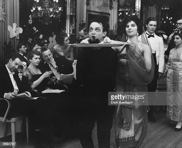 Revellers in fancy dress as Salome and John the baptist at an opera ball at the Dorchester Hotel in London. They are watched by composer, Benjamin...