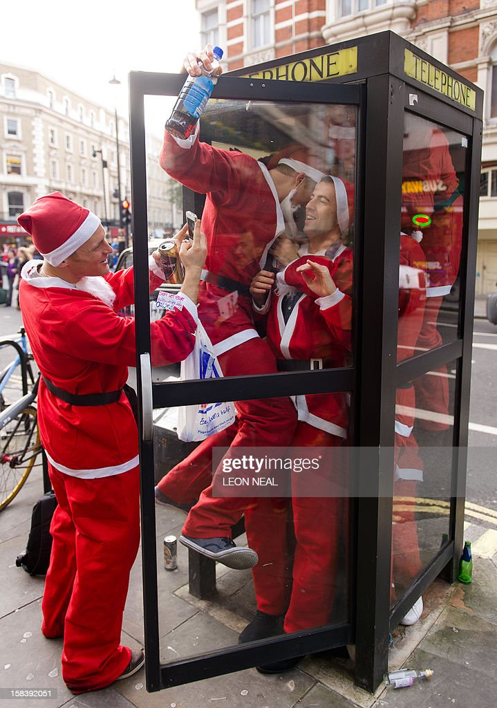 Revellers in Santa costumes jam into a telephone box during a 'Santacon' near Trafalgar Square in central London on December 15, 2012, less than two weeks before Christmas.