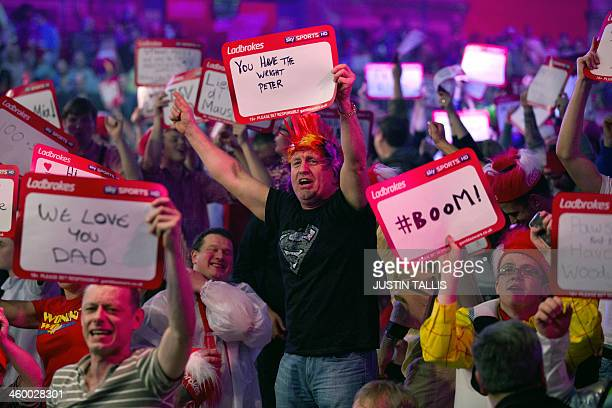 Revellers in the crowd cheer during the PDC World Championship darts final between Britains Peter Wright and the Netherlands Michael van Gerwen at...