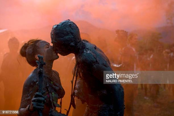 TOPSHOT Revellers kiss during the Bloco da Lama a mud carnival in Paraty Brazil on February 10 2018 Bloco da Lama started in 1986 by teenagers...