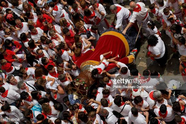 A revellers lift a girl to kiss the King Giant figure during the farewell ceremony of the Comparsa de Gigantes y Cabezudos 'Giants and Big Heads...