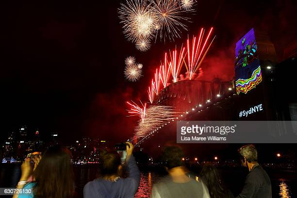 Revellers look on during the midnight fireworks display as seen on New Year's Eve on Sydney Harbour on January 1 2017 in Sydney Australia