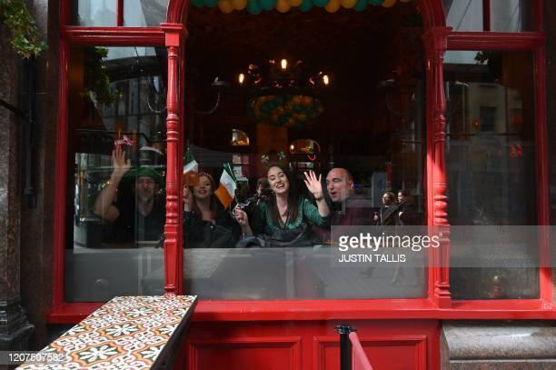 Revellers look out of the window of an Irish pub as they celebrate St Patrick's Day in central London on March 17 2020 Britain on Tuesday ramped up...