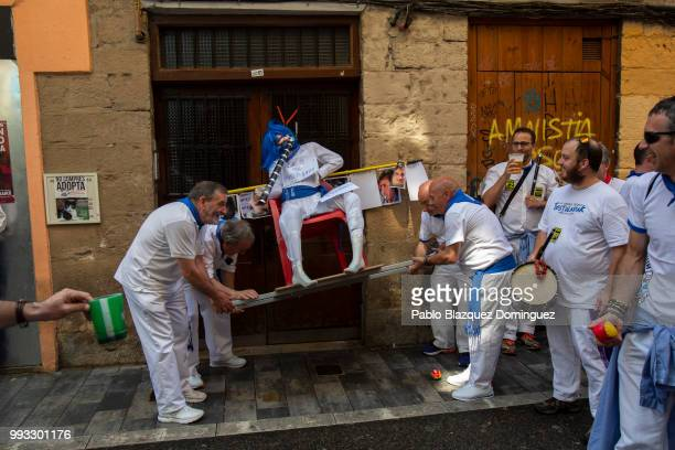 Revellers of 'la Jarana' carry along the streets a figure of a friend on the second day of the San Fermin Running of the Bulls festival on July 7...