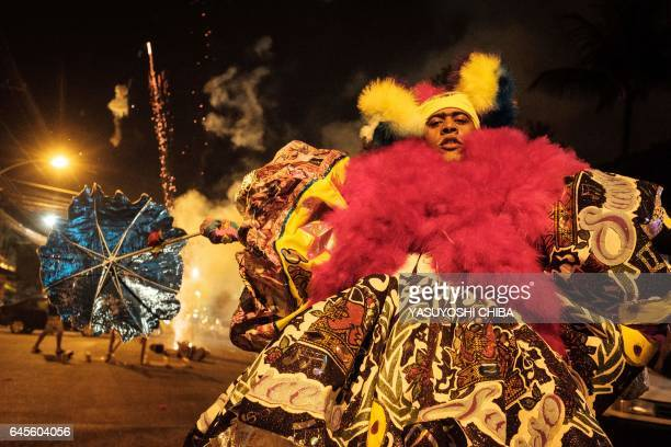 """Revellers of the """"Sucesso"""" bate-bola street carnival band fire fireworks during the first day of carnival in Rio de Janeiro, Brazil, on February 25,..."""