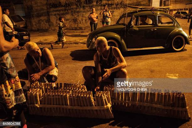 Revellers of the Sucesso batebola street carnival band set up fireworks in the first day of carnival in Rio de Janeiro Brazil on February 25 2017 The...