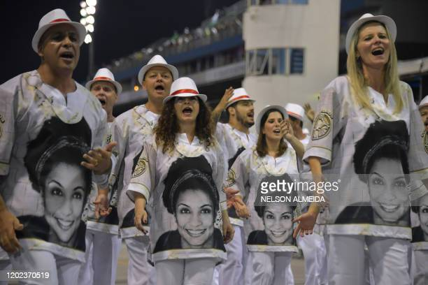 Revellers of the Tom Maior samba school wear t-shirts with photos of late Brazilian politician Marielle Franco, who was assassinated in 2018, as they...