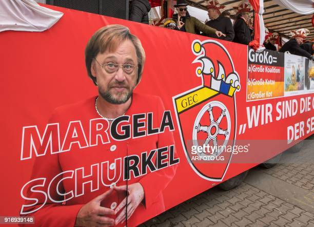 Revellers on a bus with an inscription reading 'Margela Schurkel' and a photomontage composed with the portraits of German Chancellor Angela Merkel...