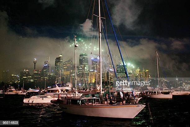 Revellers on various boats parked on the harbour look on during New Years Eve celebrations on Sydney Harbour on December 31 2009 in Sydney Australia