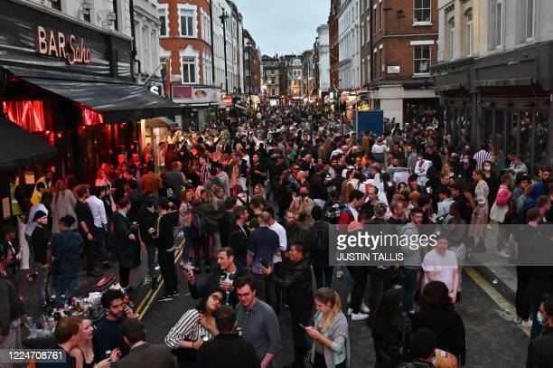 Revellers pack a street outside bars in the Soho area of London on July 4 as restrictions are further eased during the novel coronavirus COVID-19...