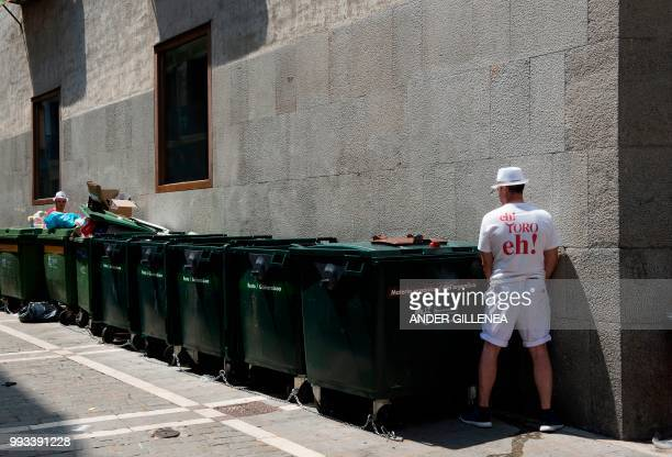Revellers pee next to garbage containers on the first day of the San Fermin bull run festival in Pamplona northern Spain on July 7 2018 Each day at...