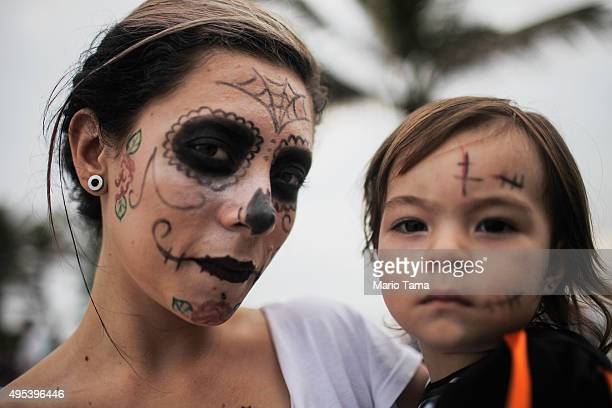 Revellers pose on Ipanema beach during Day of the Dead festivities on November 2 2015 in Rio de Janeiro Brazil Brazilians often mark the traditional...