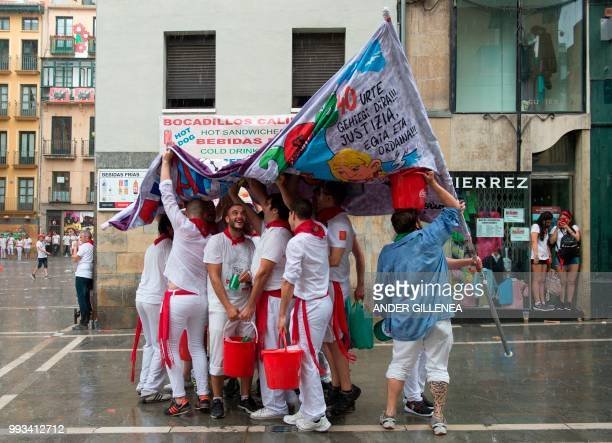 Revellers protect themselves from the rain on the first day of the San Fermin bull run festival in Pamplona northern Spain on July 7 2018 Each day at...