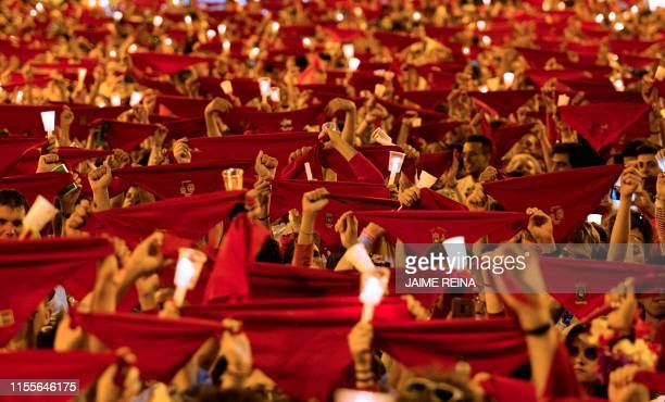 TOPSHOT Revellers raise red scarves and candles as they sing the song 'Pobre de Mi' marking the end of the San Fermin festival in Pamplona northern...